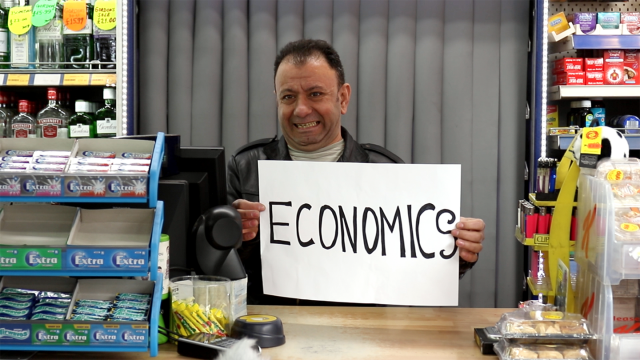 Man holding 'economics' sign in newsagents