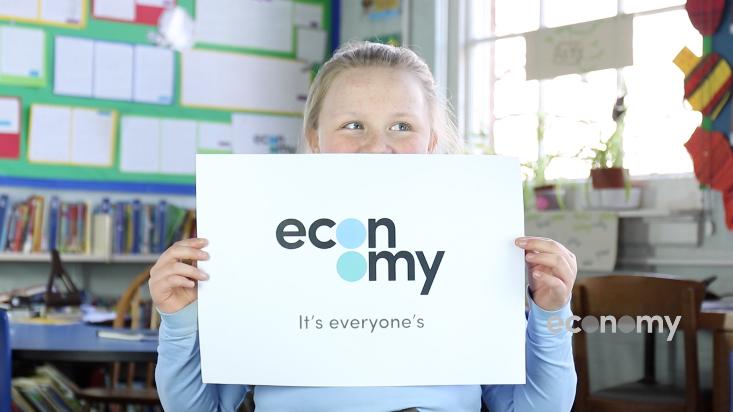 Schoolgirl holds up paper economy logo