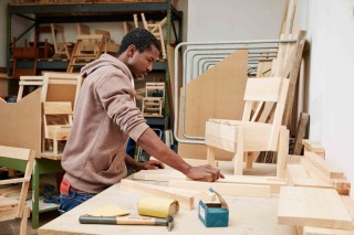 Ali Maiga Nouhou works on a child's chair at Cucula in Berlin