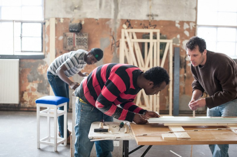 Two members of the Cucula team working on a piece of furniture