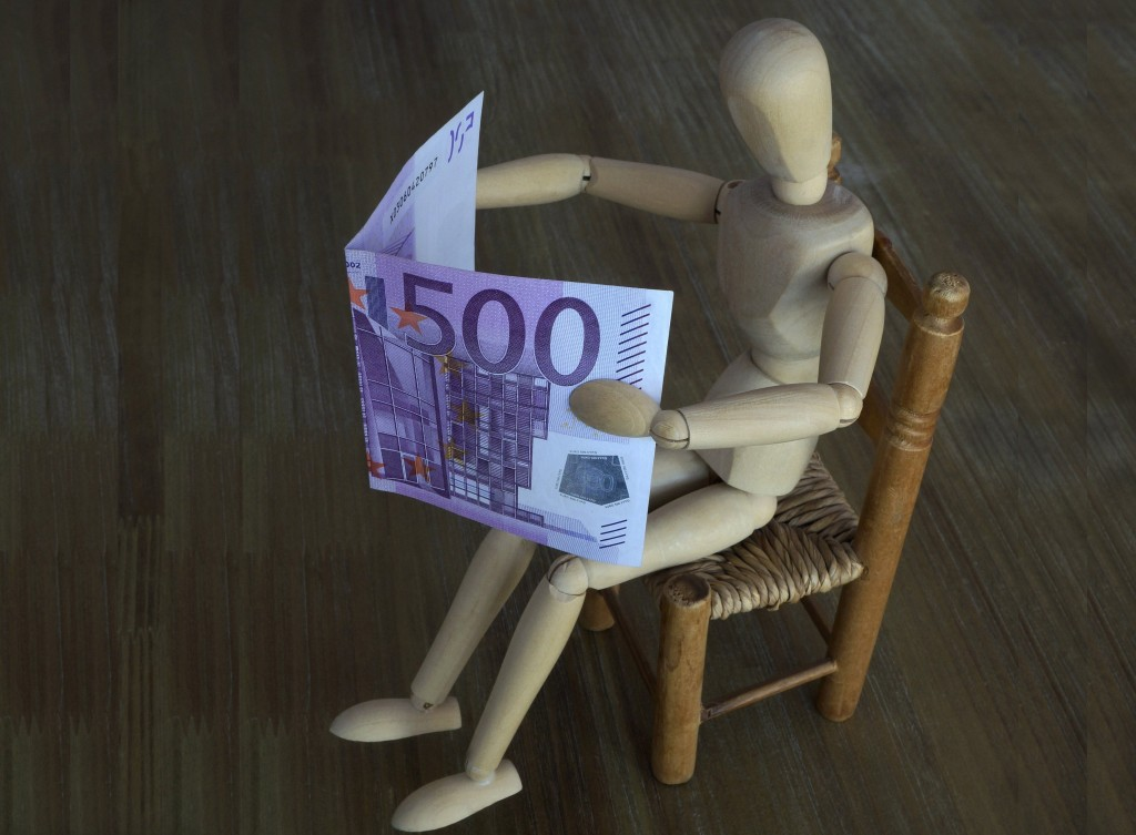 A manikin sits on a chair and reads a 500 Euro note instead of a newspaper. Credit: S. Steinach