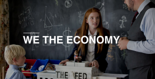 We The Economy: three people in a classroom stand around a model of the US Federal Reserve