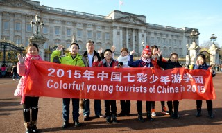A group of Chinese tourists pose for photographs outside Buckingham Palace, London