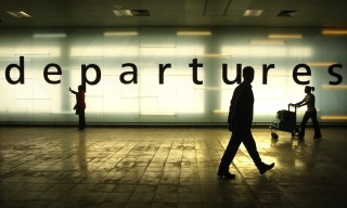 Passengers walk past a departures sign to the the new security block at Glasgow Airport, Glasgow.