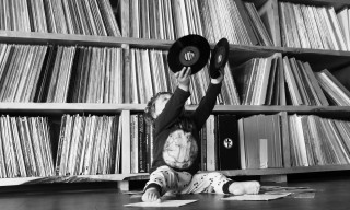 A small child sat on the floor holds up two vinyl records
