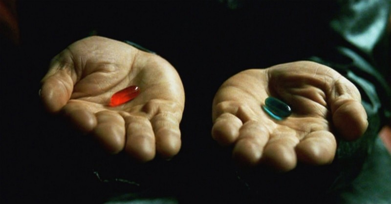A pair of hands, one holds a blue pill, the other a red pill