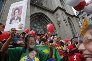 A demonstrator wearing a mask with the likeness of former Brazilian President Luiz Inacio Lula da Silva and holding a picture of Brazil's current president Dilma Rousseff protests in their support in Sao Paulo, Brazil