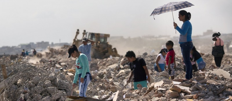 Residents comb through a field, salvaging recyclable material from post-earthquake debris, in Manta, Ecuador,.