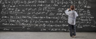 A child writes equations on a blackboard