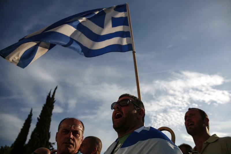Protesters in Greece stand in front of a Greek flag