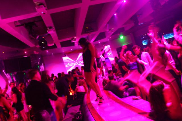 A woman dances on a bar in a nightclub