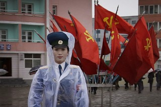 A North Korean traffic police woman directs vehicles at a street junction while behind her the sidewalk is decorated with flags of the ruling party