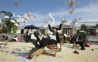 A protestor throws fake money into the air as she relaxes on a deckchair in an interactive, tropical tax haven beach in Trafalgar Square in London