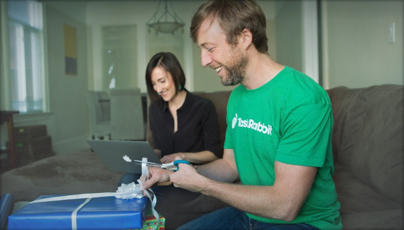A Taskrabbit worker wraps a present, while a woman sits next to him working on her laptop