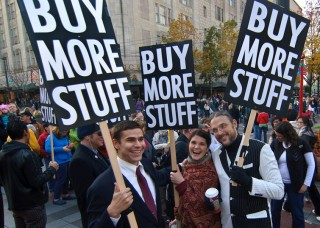 People hold placards that say 'Buy More Stuff'