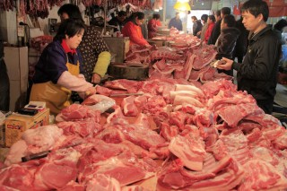 Local residents choose pork at a market in Nanjiang in east China's Jiangsu province