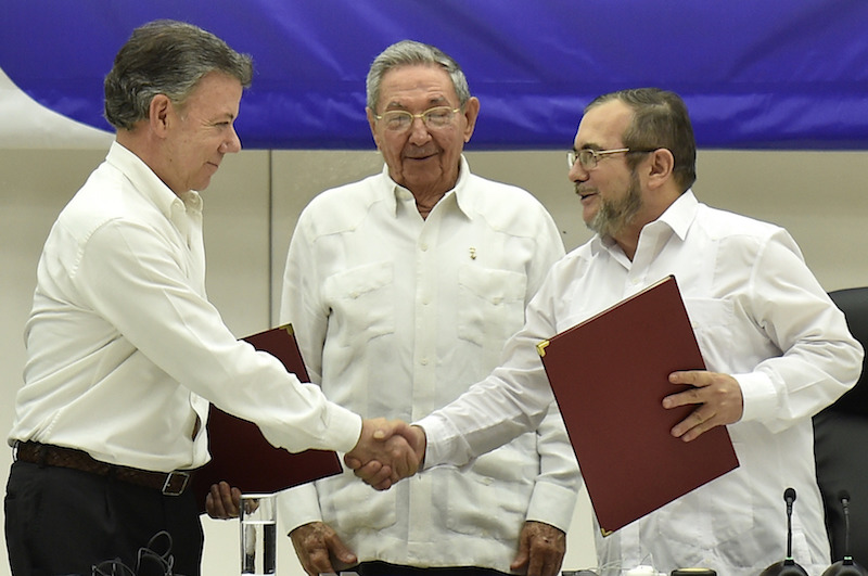 Colombian President Juan Manuel Santos (L) shakes hands with Timoleon Jimenez (R), the top leader of the Revolutionary Armed Forces of Colombia (FARC), next to Cuban President Raul Castro, in the signing ceremony of a historic ceasefire agreement between the Colombian government and the FARC, in Havana, capital of Cuba, on June 23, 2016.