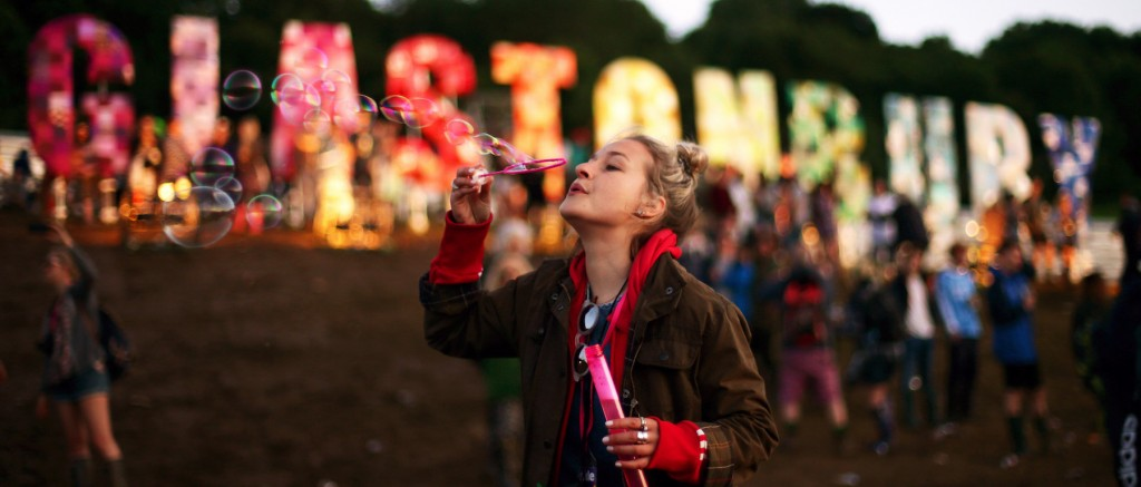 A festival-goer blowing bubbles in front of the Glastonbury sign at the Glastonbury Festival