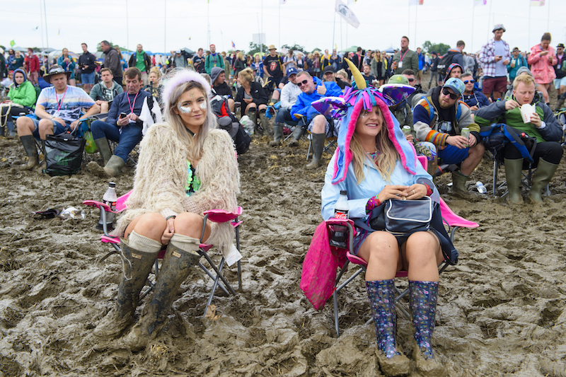 The crowd at the Glastonbury Festival sit on chairs in the mud, at Worthy Farm in Somerset.