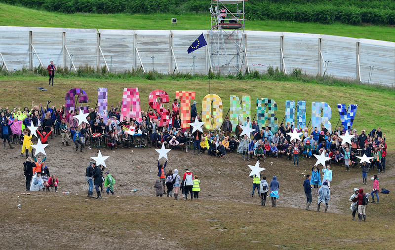 A flash-mob gather in front of the Glastonbury sign at Glastonbury Festival 2016