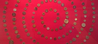A circle of coins on a red background, part og the Money Matters exhibition at the British Museum