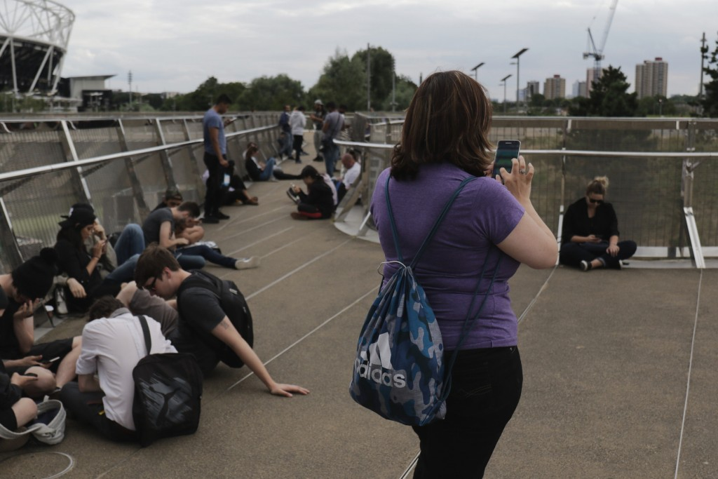A young woman plays Pokemon Go at the Olympic Stadium, London.