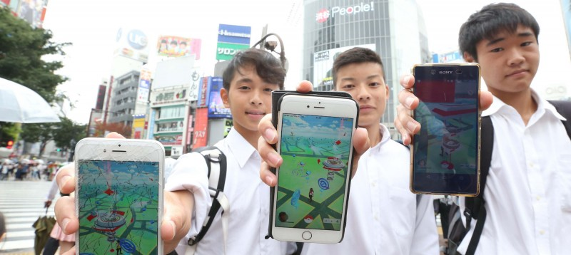 Three teenage boys hold up their phones while playing Pokemon Go