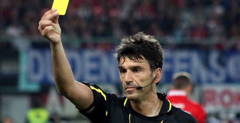 A soccer referee shows a yellow card