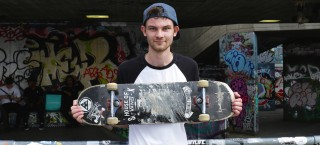 A skater stands with his board on the Southbank in London