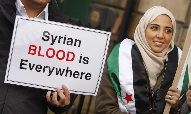 A man and woman hold a sign saying 'Syrian blood is everywhere'