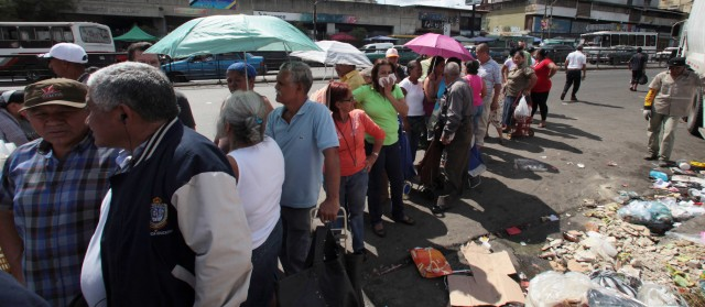 People line up to buy government subsidized food at a state-run market in Venezuela
