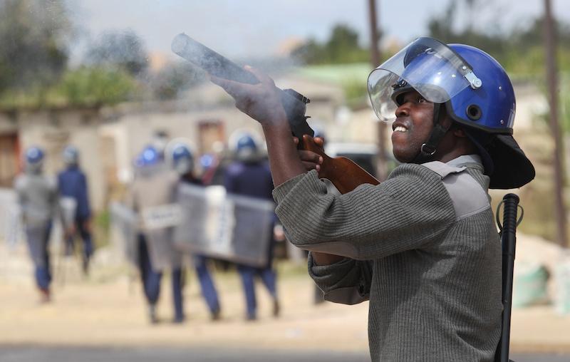 Armed policeman fires a tear gas gun in Zimbabwe Riots