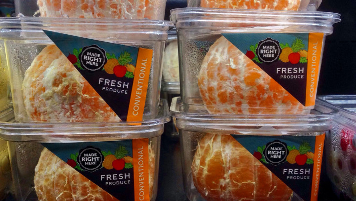 Some pre-peeled oranges on a shop shelf
