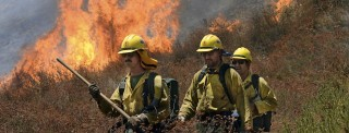 California Firefighters walk ahead of flames engulfing the bush