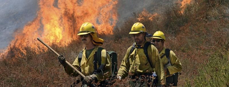 California Firefighters walk ahead of flames engulfing the bush