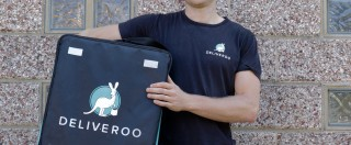 A Deliveroo driver holds his delivery box