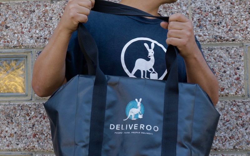 A Deliveroo driver holds his delivery bag