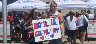 Two soccer fans hold a sign that reads: 'Equal Play Equal Pay'
