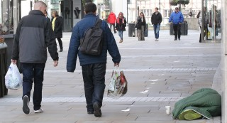 Shoppers pass a homeless man in Manchester