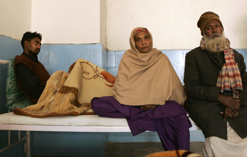 Shakel Ahmed, 28, left, whose kidney was removed, recovers at city civil hospital as his mother father sit near him, in Gurgaon, on the outskirts of New Delhi, India