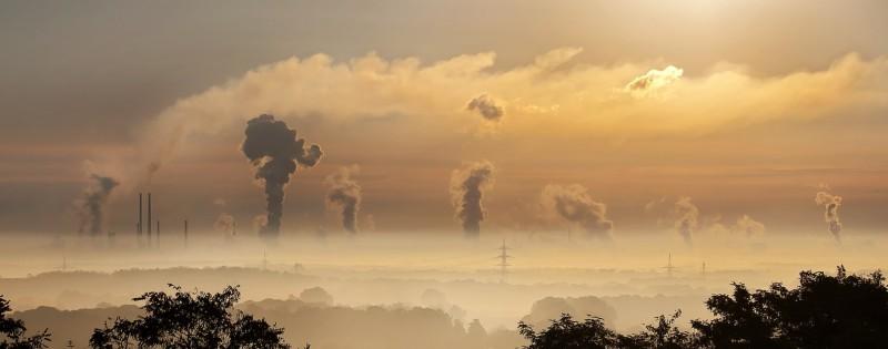 Chimneys emit smoke into the sky