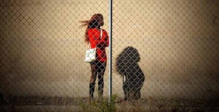 A Nigerian sex worker stands behind a fence in Italy