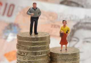 Two plastic models, one man, one woman, stand on top of piles of pound coins