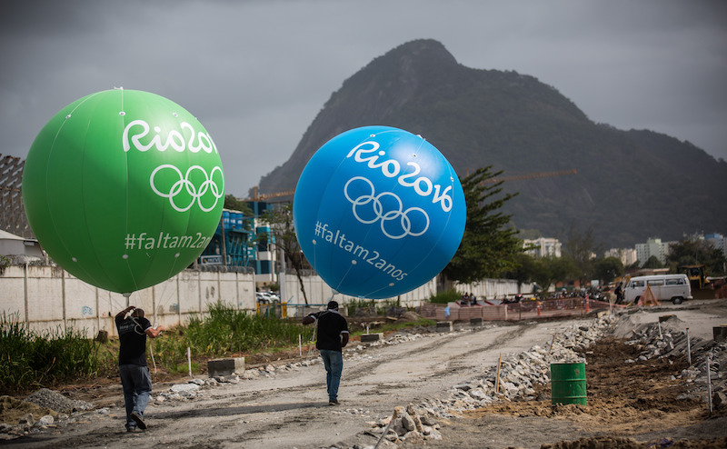 Workers with large balloons, featuring the writing 'Rio 2016', walk past the olympic park in Rio