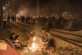 Refugees sit round a campfire in Idomeni