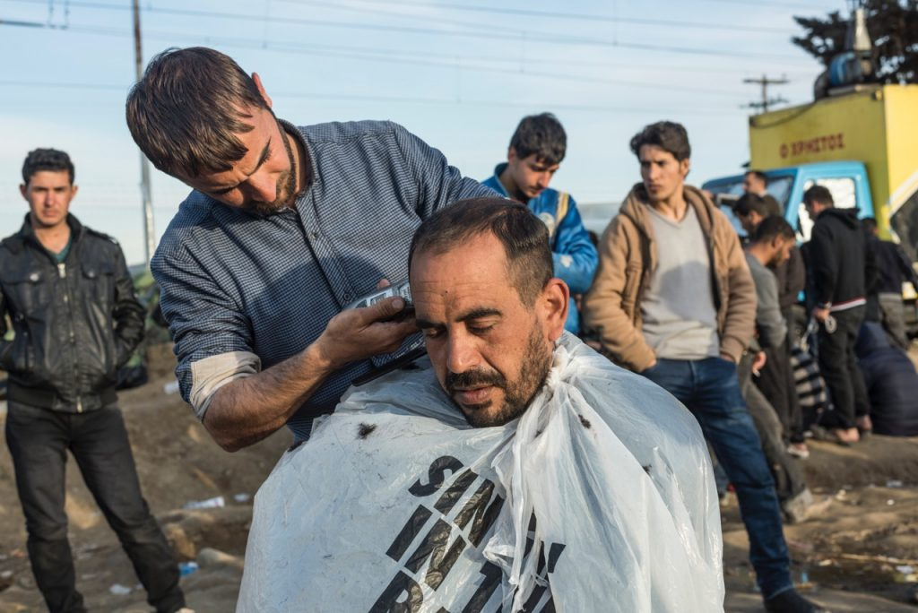 A man has his haircut at the Idomeni refugee camp