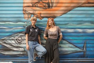 Two women in front of a garage in Greece.