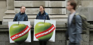 Two people protest about lack of tax Apple pay in Ireland