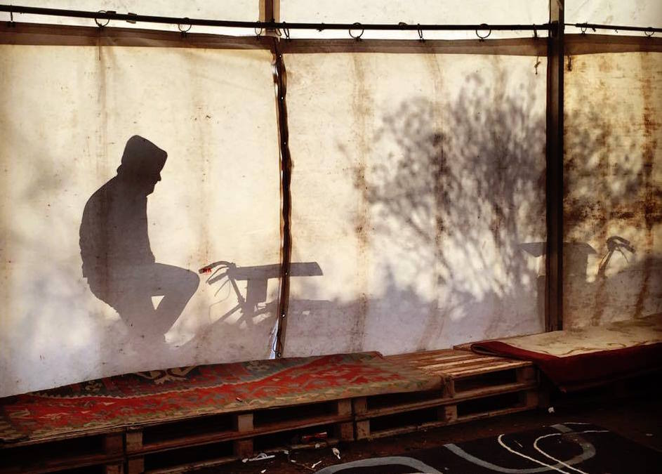 A man on a bike generates electricity at a refugee camp