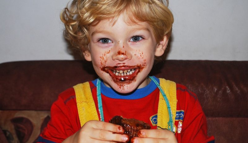 A young boy whose face is covered in chocolate, eating a muffin